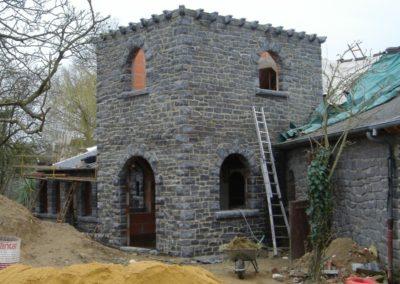 Tour en pierre rectangulaire, avec corbelets, appuis, arcs plein cintre et seuils taillés sur place.