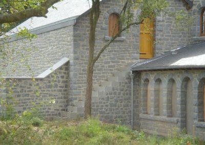 Arrière du garage maçonné en pierre et pose d'un escalier en granit accolé à côté d'une coursive qui est composée d'une succession d'arcs plein cintre ( 8 au total).