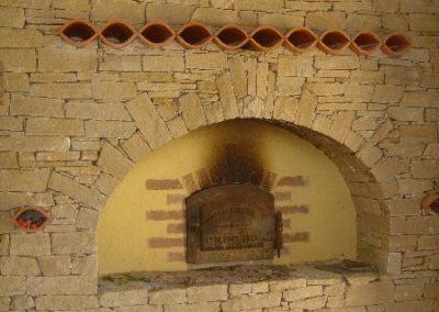 Maçonnerie d'une façade d'un four à pain en pierres sèches (type gneiss beige) avec tuiles canal en décoration.