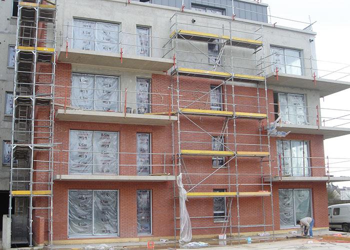 Pose de plaquettes rouge sur la façade d'un immeuble